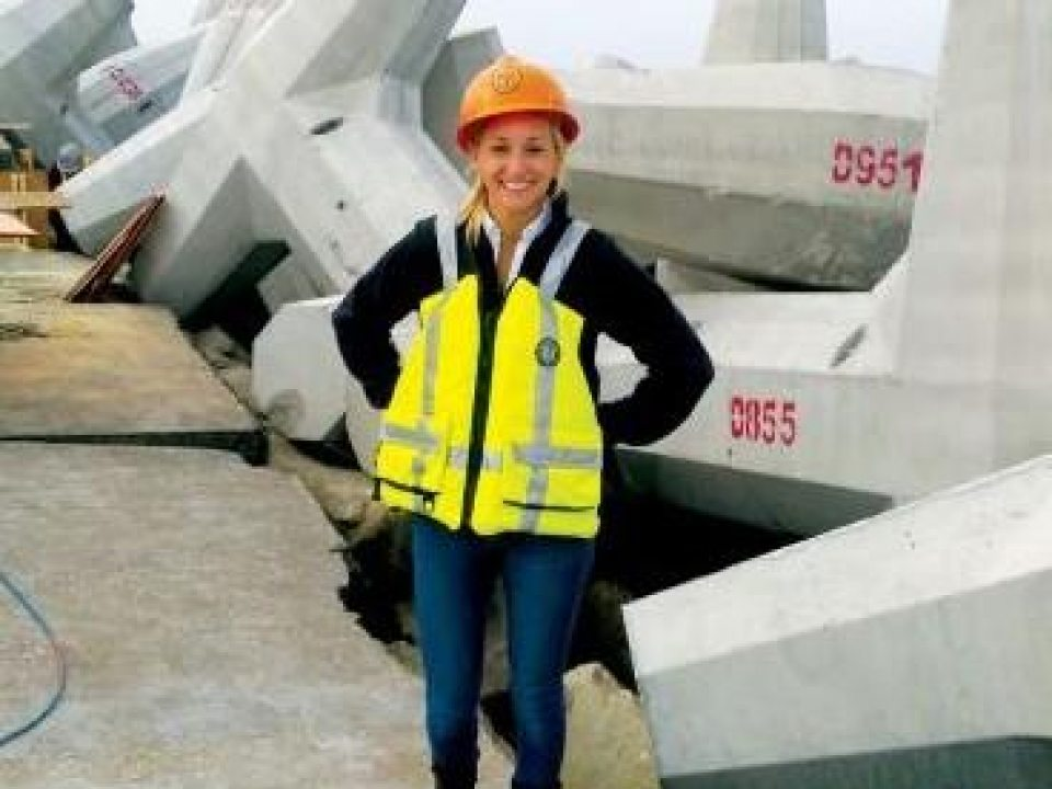 an female student intern, wearing a yellow vest and orange hardhat, standing in front of construction materials