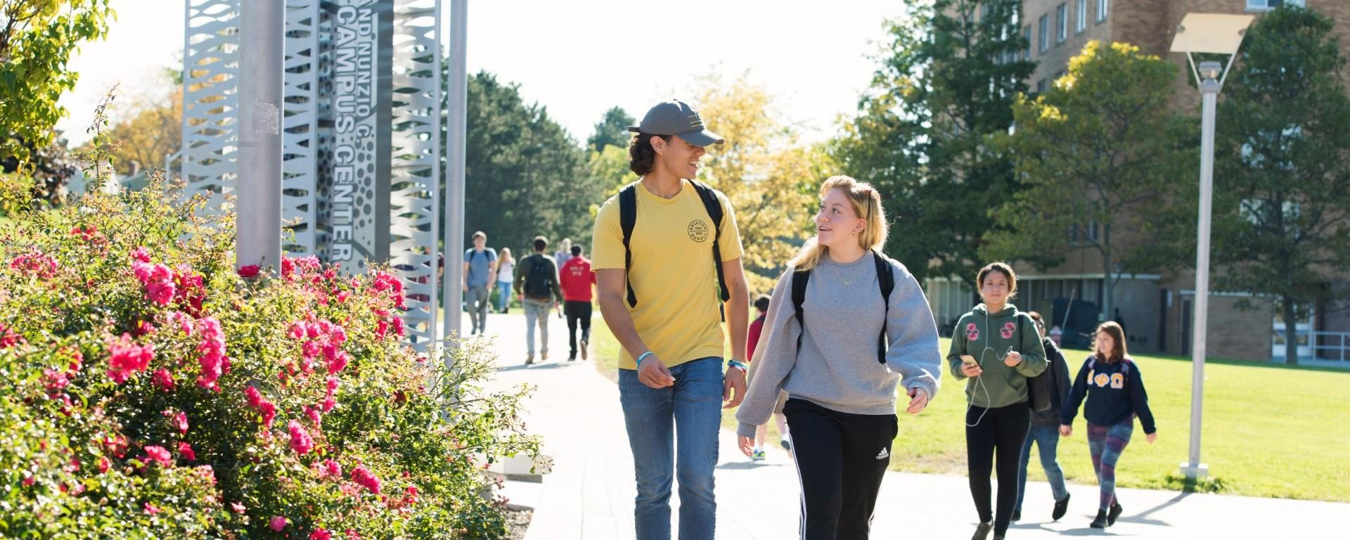 Students seen walking along the sidewalk in front of the Marano Campus Center