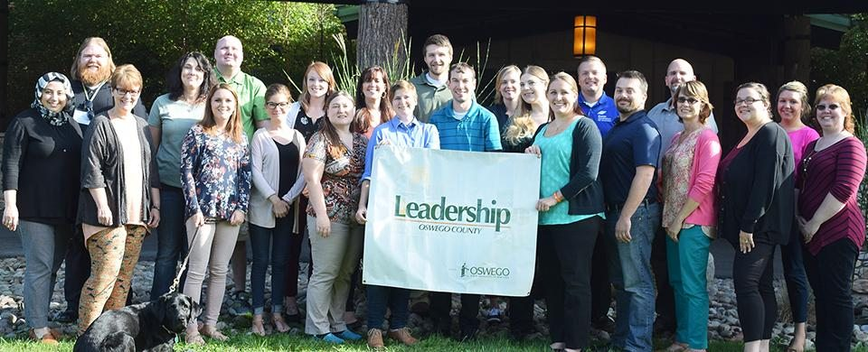 A group of people holding the Leadership Oswego County banner